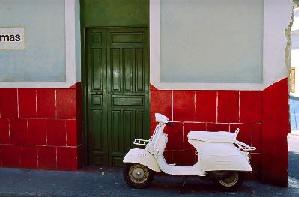 white vespa in front of colorful housefacades